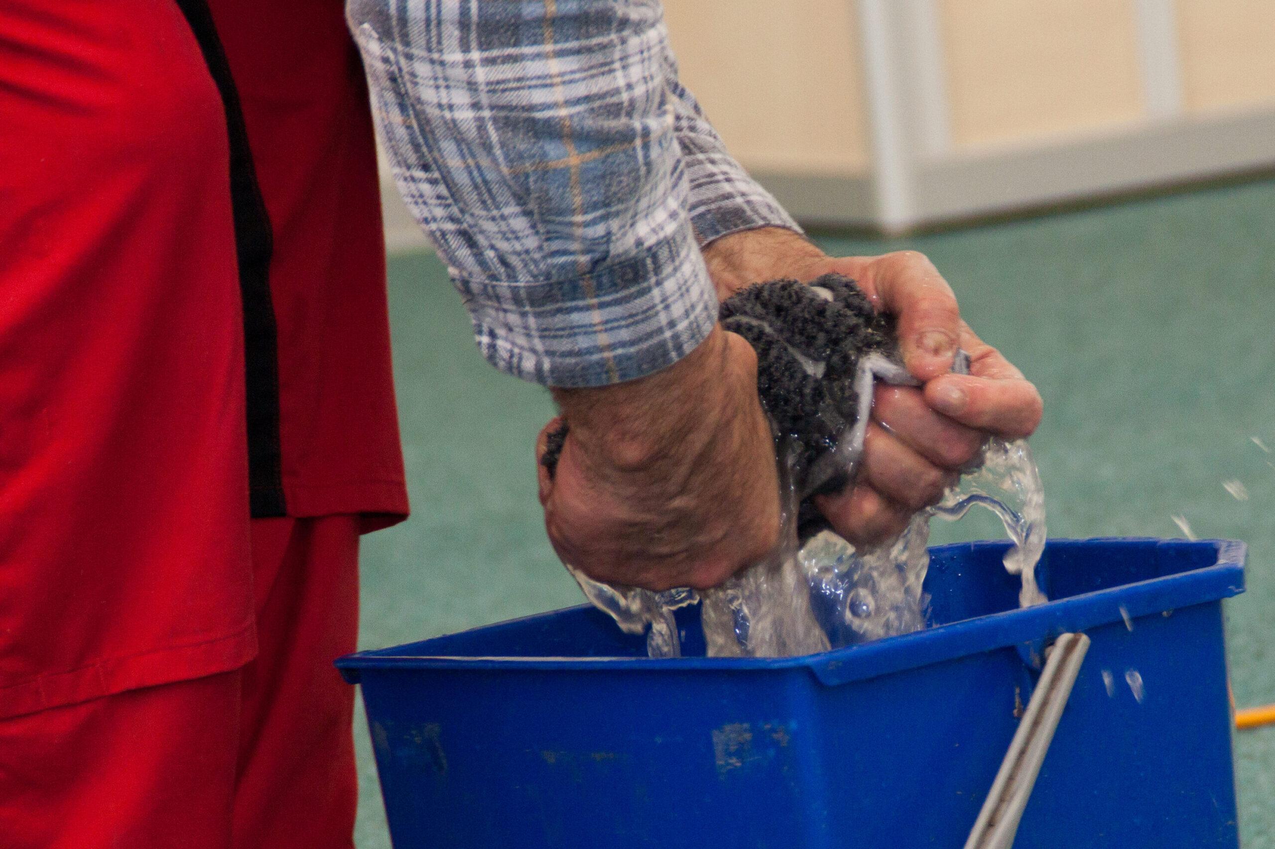 Mitarbeiter der RSN GmbH wringt einen nassen Mop über dem Eimer aus